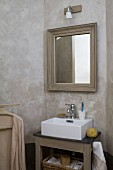 Walls marbled in umber in washing area; framed mirror above country-house washstand with modern countertop sink