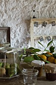 Pears under glass cover, freshly picked lemons and jars of jam in front of old wooden frames on roughly plastered wall