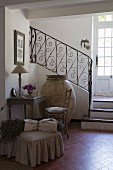 Small antique desk and chair, huge old olive amphora and bunch of lavender on pouffe on terracotta tiles at foot of staircase with wrought iron balustrade