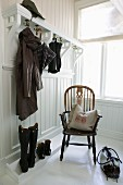 Windsor chair with scatter cushion in white-panelled cloakroom; high boots, raincoat and umbrella