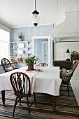 Erdbeerpflanze auf Esstisch und Windsor-Stühle in Wohnküche mit Holzverkleidung