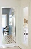 View into bedroom and bathroom with pale blue, panelled walls and chair with black and white upholstery