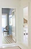 Blick in Schlafraum und hellblau vertäfeltes Badezimmer mit schwarz-weiss kariert gepolstertem Antikstuhl
