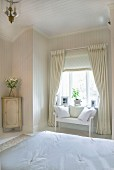 Elegant, country-house-style bedroom - view across double bed to delicate wooden bench below window