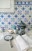 Traditionelle, blau-weisse Fliesen, Handspiegel und Keramik auf der Steinplatte eines Waschtischs