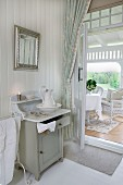 View from bedroom with traditional washstand through open door to seating area in conservatory