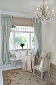Chandelier above elegant seating area with delicate, white antique furniture in front of traditional, Scandinavian window with curtains