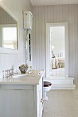 Washstand in Scandinavian, shabby-chic bathroom with view into adjoining bedroom