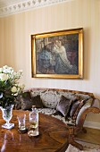 Oil painting above Biedermeier sofa, white roses in glass goblet and aperitif on table in foreground
