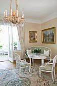 Sitzgruppe mit zierlichen, weissen Möbeln im Antikstil in Raumecke vor goldgerahmten Ölgemälden, vorne Kronleuchter und Seidenteppich