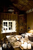 Set table in dining room lit by lamps and candles in rustic wooden cabin