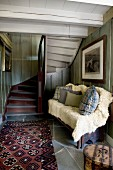 Cushions and pale fur blanket on bench next to rug at foot of winding wooden staircase in rustic foyer