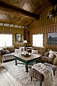 Comfortable seating area with ottoman, sofas and coffee table in rustic living room in wooden house