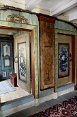 Foyer with painted walls in old wooden house and view of cabinet through open door