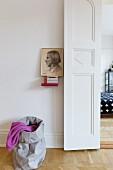 Blick vom Wohnraum mit Portraitbild und Sack auf die Flügeltür zum Schlafraum