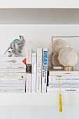 Books and ornaments on white wall-mounted shelf