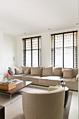Ecru armchairs and couch below window with half-closed louvre blinds in modern interior
