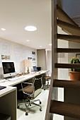 Arbeitszimmer mit langem Schreibtisch an Wand und Bürostühle im Klassikerstil, abgehängte Decke mit integrierter Beleuchtung, seitlich Treppenaufgang