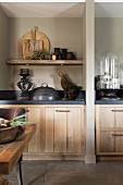 Kitchen counters with dark worksurfaces and wooden fronts separated by partition