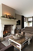 Rustic coffee table with curved legs in front of open fire below Christmas arrangement with lit candles on mantelpiece