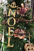 Christmas tree decorated with festive motto in gold letter ornaments