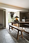 Rustic wooden table and bench set in modern interior with open interior shutters on terrace door in background