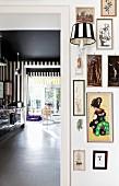 Eklektische Bildersammlung mit Wandleuchte, Blick in Küche und Essbereich mit schwarz-weißer Streifentapete und schwarzer Deckenfarbe