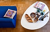 Various bowls on retro coffee table with white top next to blue easy chair on mosaic parquet floor