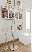 Objets d'art next to white cubic stool on tiled floor below gallery of artworks on wall