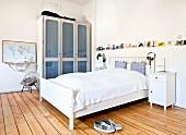 Weißes Doppelbett mit Kopfteil und Vitrinenschrank in ländlichem Schlafzimmer mit Dielenboden und nostalgischem Flair