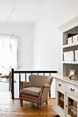 Sessel mit naturfarbenem Bezug vor Holz-Treppengeländer, nostalgische weiße Anrichte auf Galerie mit ländlichem Flair