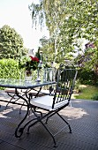 Metal chair with white seat cushion at outdoor table on wooden terrace in sunny garden