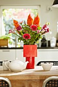 Blumenstrauss aus Gerbera und Calla in verschiedenen Rottönen in roter Vase auf Esstisch
