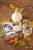 Branches of colourful autumn leaves in white ceramic vases amongst leaves and postcard scattered on wooden surface