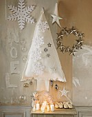 Christmas arrangement: candles, white fabric fir tree, stars and dolls' shoes