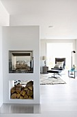 Masonry fireplace in open-plan minimalist interior with Lounge chair and footstool in background