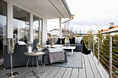 Upholstered furniture with blankets and side table on balcony