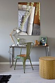 Console table and green retro metal chair against grey-painted wall