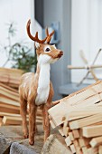 A decorative young deer between planks of wood