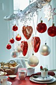Hearts and Christmas tree baubles in red and white hanging on a branch over a breakfast table