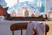 Avents decorations – house lanterns and wooden house on a driftwood board on a window sill