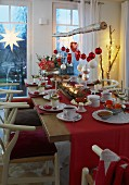 A festively laid Christmas table in red and white with a branch of Christmas ornaments hanging above it