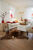 A country-style living room decorated for Christmas with red stars in the windows, a white two piece suite and an upholstered coffee table