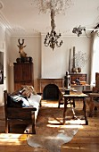 Rustic atmosphere in renovated period apartment with stucco ceiling, wooden bench, simple table on animal-skin rug and hunting trophy in background