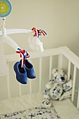 Hand-crafted mobile with miniature Dutch clogs above cot