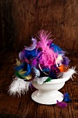 Easter arrangement of colourful feathers in bowl