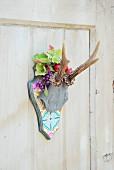 Stilisiertes Tiergeweih auf gemusterter Platte in stilisierter Kopfform, dekoriert mit Blättern und Obst aus Plastik
