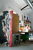 Detail of studio - woman at workbench, wrapped artwork and plan chest in foreground