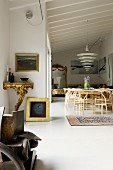 Designer Enigma pendant lamp above dining set with classic chairs; antique, Rococo, gilt console table to one side in open-plan interior