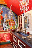 Indian-style mural on wall of traditional kitchen with ornate chandeliers with crystal pendants above kitchen counter